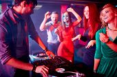 Male deejay adjusting sound with group of cute girls dancing near by