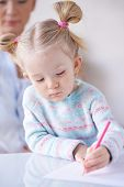 Little girl in casualwear drawing with crayon