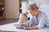 Cute child and her mother with digital tablet relaxing at home