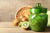 Tasty kiwi jam in glass jar on wooden background