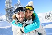 image of snowy hill  - Man giving piggyback ride to girlfriend in snowy mountain - JPG