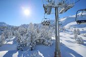 Back view of skiers in chairlift in snowy mountain