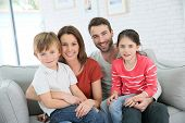 Cheerful family at home sitting in sofa