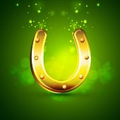 Golden horseshoe on shiny green background for Happy St. Patrick's Day celebration.