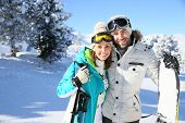 Cheerful couple of skiers standing in snowy mountain
