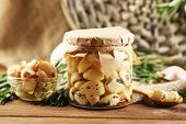 Canned garlic in glass jar, wicker mat and rosemary branches  on wooden background