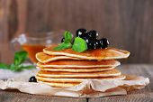 Stack of pancakes with mint and berries on rustic wooden background