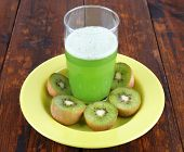 Glass of green smoothie with pieces of kiwi on plate on wooden table background
