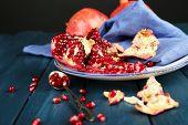 Juicy ripe pomegranates on wooden table, on dark background
