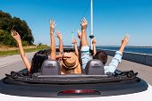 picture of road trip  - Rear view of young happy people enjoying road trip in their convertible and raising their arms up - JPG