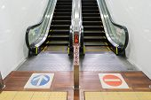 stock photo of escalator  - an escalator upstair way and downstair way with sign on the floor - JPG