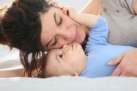 stock photo of cuddle  - Portrait of mother cuddling baby boy - JPG