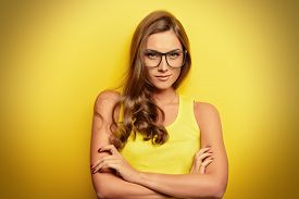 image of yellow  - Beauty portrait of a happy young woman in spectacles and bright yellow dress over yellow background - JPG