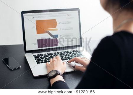Shot of a young lady working with laptop, woman\'s hands on notebook computer and smart phone, buisin