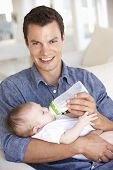 stock photo of feeding  - Young Father With Baby Feeding On Sofa At Home - JPG