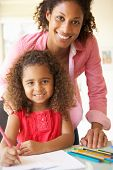 stock photo of homework  - Mother Helping Daughter With Homework At Home - JPG