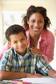 image of homework  - Mother Helping Son With Homework At Home - JPG
