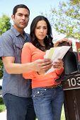 picture of mailbox  - Worried Hispanic Couple Checking Mailbox - JPG