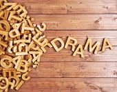 stock photo of drama  - Word drama made with block wooden letters next to a pile of other letters over the wooden board surface composition - JPG