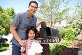 stock photo of mailbox  - Hispanic Father And Son Checking Mailbox - JPG