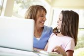 image of grandmother  - Hispanic Grandmother Using Laptop And Calculator With Granddaughter - JPG