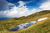 stock photo of cumulus-clouds  - Cumulus cloud over the mountain ridge reflected in a small lake - JPG