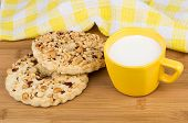 picture of shortbread  - Two shortbreads rings with peanuts and cup of milk on wooden bamboo table - JPG