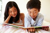 stock photo of pre-teen boy  - Young Asian girl and boy reading book - JPG