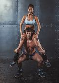 foto of squatting  - Athlete muscular sportsman doing exercising squats with woman sitting on his shoulders Crossfit fitness sport training lifestyle bodybuilding concept - JPG