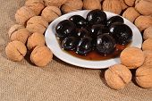 foto of walnut  - Jam from walnuts on a saucer and walnuts on a sacking background - JPG