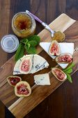 picture of jar jelly  - Fresh figs on wooden cutting chopping board with jar of fig jelly preserve and gourmet cheese on dark wood rustic table background overhead view - JPG