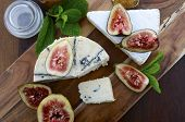stock photo of jar jelly  - Fresh figs on wooden cutting chopping board with jar of fig jelly preserve and gourmet cheese on dark wood rustic table background overhead view - JPG