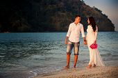 foto of barefoot  - brunette bride and handsome groom barefoot walk at sand beach at dawn - JPG