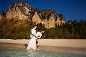 stock photo of barefoot  - groom holds bride in arms barefoot at edge of transparent water against cliffs - JPG