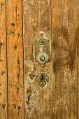 picture of keyholes  - Closeup take of the wooden planks of and old door and its keyhole - JPG