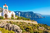 stock photo of greek-island  - Iconic church with red roof on cliff over sea bay on Greek island - JPG