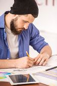 image of draft  - Goodlooking man dressed casual sitting at the table and drawing draft - JPG