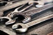image of workbench  - Collection of used dirty old grunge metal wrenches and spanners lying on a workbench in an engineering workshop close up view of the jaws - JPG