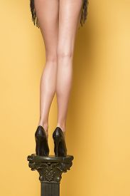 stock photo of slender  - Slender long legs of young girl in black shoes on high heels standing on yellow wall background vertical picture - JPG