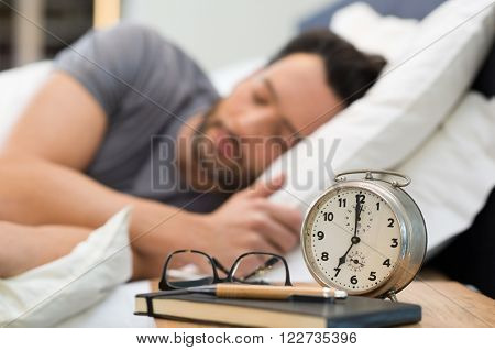 Young man sleeping in his bedroom. Man sleeping with an alarm clock in foreground. A calm man in his