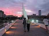 Two Women Crossing The Puente De Las Mujeres, The Bridge Of Women, At Sunset