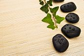 Ivy branch and spa stones arranged on bamboo board