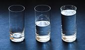 stock photo of glass water  - three glasses empty half and full with water on dark blue background - JPG