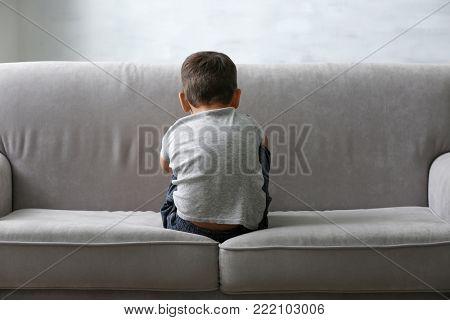 Little boy sitting on sofa