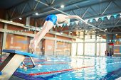 Adolescent boy in swimwear doing jump into water of swimming-pool from diving board poster