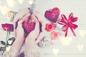 Valentine Gift. Young Couple Hands holding red heart gift over wooden background. St. Valentines Da poster