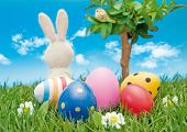 easter-bunny with coloured eggs sitting in a meadow beside a tree looking into the blue sky