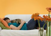 picture of young women  - young woman sleeping on a sofa with a little cat - JPG
