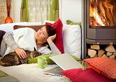 woman with a cat relaxing beside a fireplace.