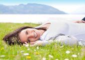 mujer joven en un prado frente a un lago